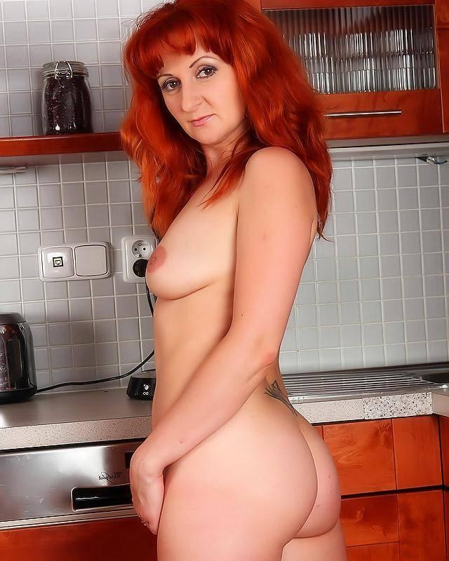 Женщина с копной рыжих волос голая решила приготовит ужин.
