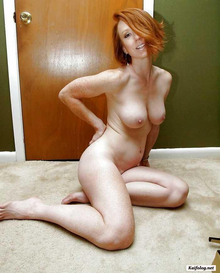 Милая зрелая женщина с стройной фигурой голая сидит на полу.