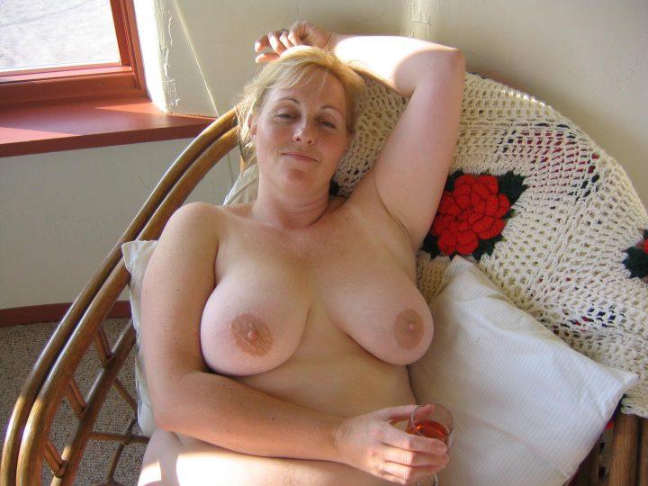 Зрелая женщина слегка в опьянении лежит в кресле с голыми сиськами