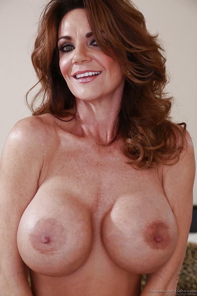 Сексуальная длинноволосая милфа с большой силиконовой грудью и красивой улыбкой